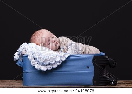 Newborn baby sleeping inside trolley bag against black background