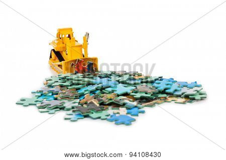 Toy bulldozer and puzzle isolated on white background