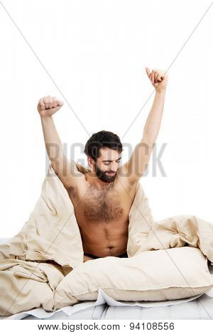 Young man waking up in bed and stretching his arms