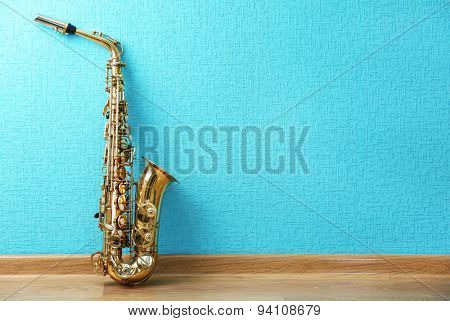 Saxophone on turquoise wallpaper background