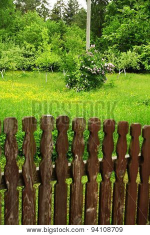 Wooden fence over green garden background