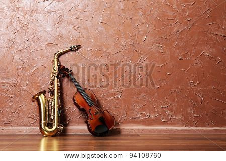 Saxophone and violin on brown wall background