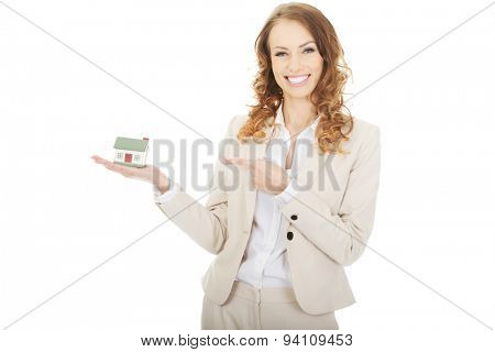 Smiling businesswoman pointing on a model house.