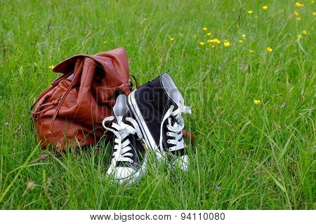 Sneakers and backpack on green grass background