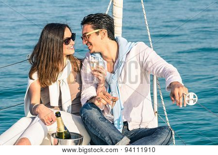 Young Couple In Love On Sail Boat With Champagne Flute Glasses - Happy Exclusive Lifestyle