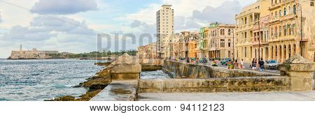 HAVANA,CUBA - MAY 3:2015 : The Malecon seawall in Havana with a view of old buildings, people and old cars