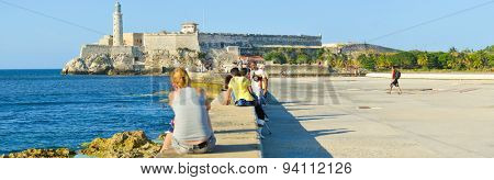 HAVANA,CUBA - APRIL 14:2015 : People at the Malecon seawall in Havana with a view of El Morro castle