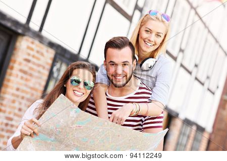 A picture of a group of happy friends sightseeing Gdansk with map