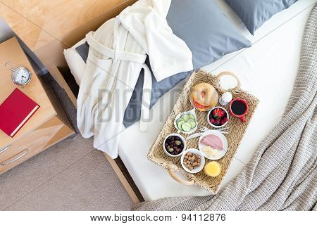Bathrobe And Breakfast Tray On Unmade Bed
