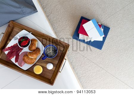 Books On Floor Beside Bed With Breakfast Tray