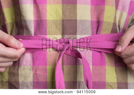 Woman Tying Pink Apron