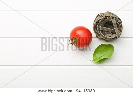 tagliatelle pasta with tomato and basil leaf on kitchen table