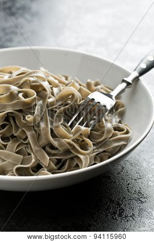 cooked black tagliatelle pasta on plate
