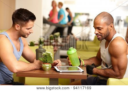 Athletic young men sitting at table in gym, taking a break, drinking refreshment, using tablet computer.