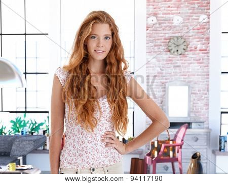 Smiling redhead woman posing for portrait at home.