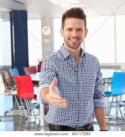 Happy casual businessman offering hand in meeting room at office.