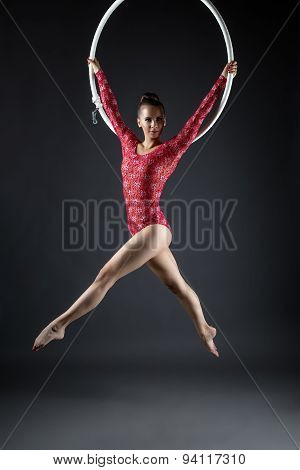 Lovely gymnast posing while performs with hoop