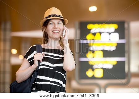 Woman Making Call In Front Of Information Board In Airport