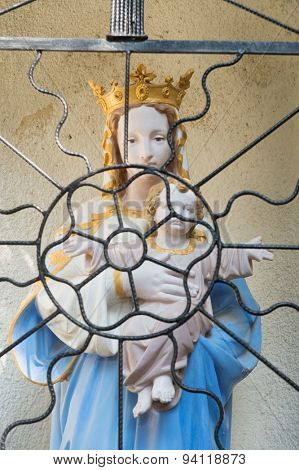 Holy Mary with child Jesus in French chapel behind fence