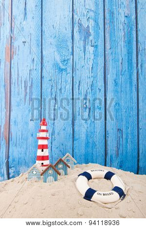 Beach with lighthouse and life buoy in front of vintage blue background