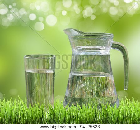 glass of water on a background of green grass