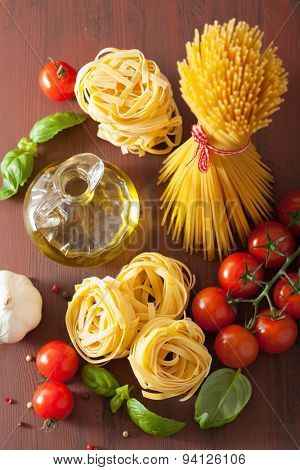 raw pasta olive oil tomatoes. italian cuisine in rustic kitchen
