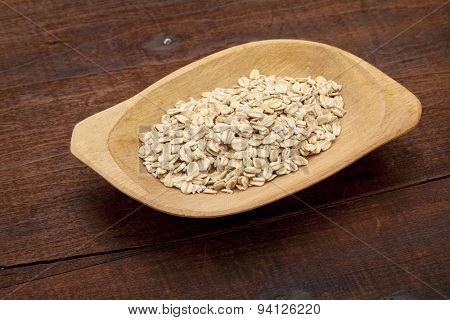 rolled oats on a rustic wooden bowl against old and cracked table
