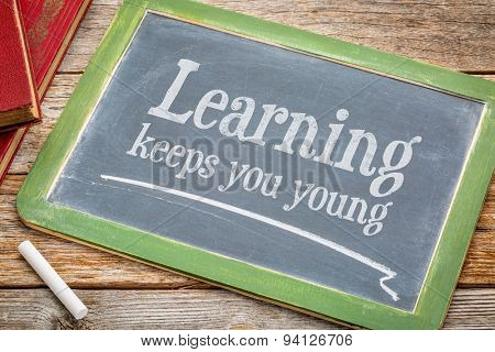 learning keeps you young - inspirational words with a white chalk on a blackboard with a stack of books against rustic wooden table