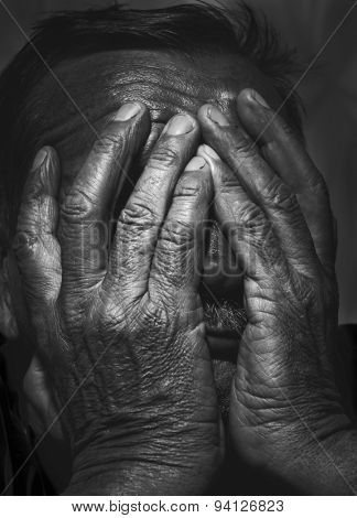 portrait of senior man covering his face with his hands. black and white image
