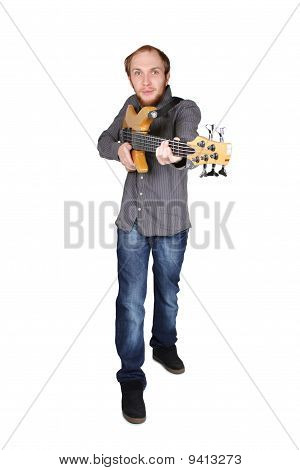 Young Man With Beard In Grey Shirt And Jeans Playing Bass Guitar And Pointing For Fingerboard At Fro