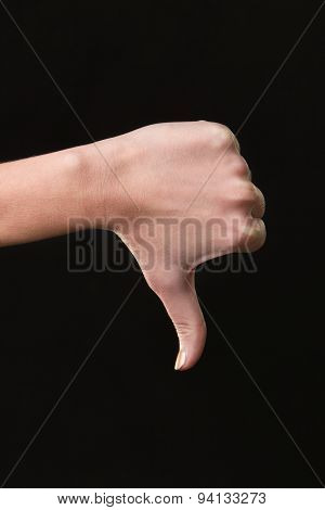 Thumb down female hand sign isolated on a dark background