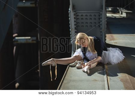 Ballerina sitting on the edge of bridge