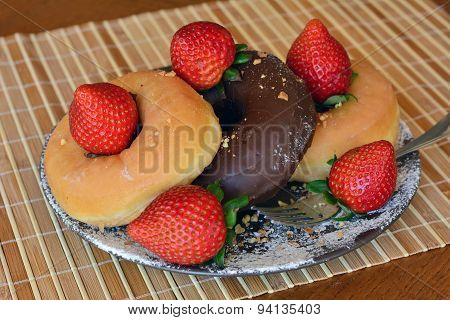 Traditional  donuts  with brown chocolate and fresh strawberries