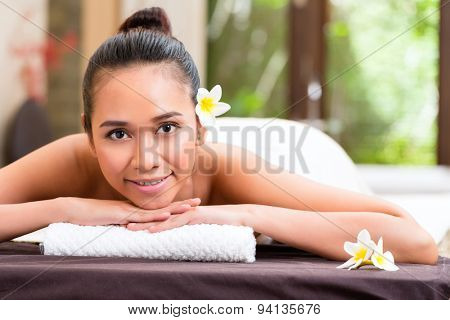 Indonesian Asian woman in wellness beauty day spa having aroma therapy massage with essential oil, looking relaxed