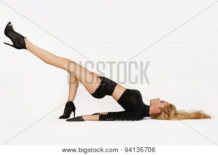Beatiful Woman With Long Legs And Blond Long Hair Lies In Difficult Position,with Raised Leg