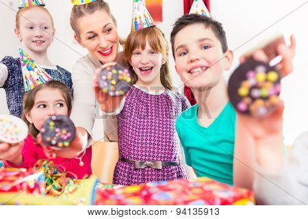 Kids showing muffin cakes into the camera at birthday party, larger group of children and mother