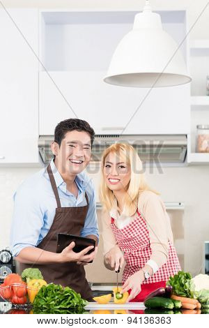 Asian couple cooking after recipes from tablet computer