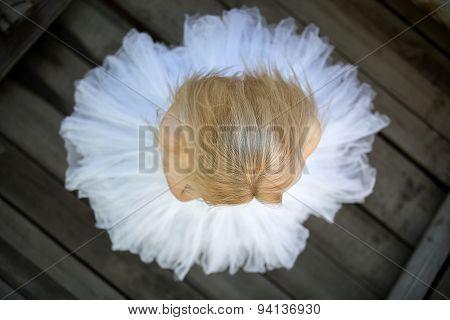 Close portrait of a cute ballerina in white tutu and blue bathin