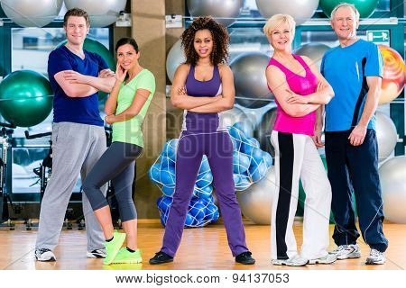 Diversity fitness group in gym, old and young, black and white people, doing sport in gymnastic training