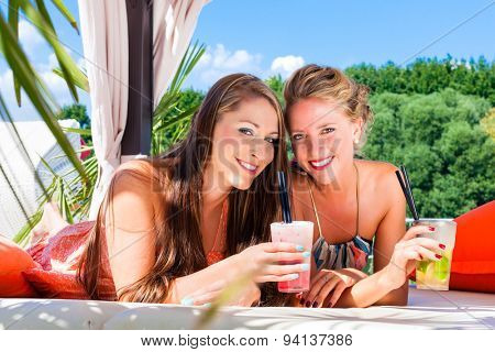 Two woman lying in the sand on the beach, drinking fancy cocktails and tanning in the sun