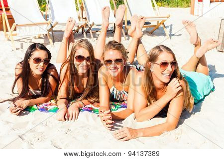 Four woman lying on beach sand, tanning in the sun