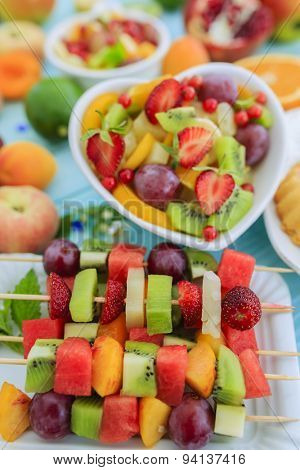 Healthy fruit salad, fruit skewer, strawberry tart - summer party