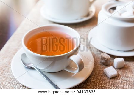 Cup Of Tea And Tea Pot On Table
