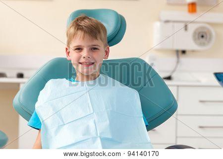 portrait of little boy sitting in dentist's office