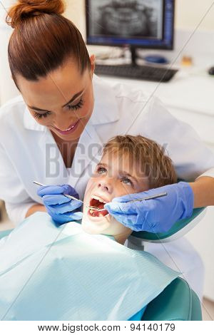 professional female dentist examining little patient