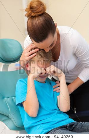 loving mother comforting her crying son in dentist office
