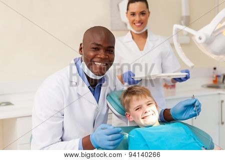 portrait of professional medical team and young patient during dental checkup