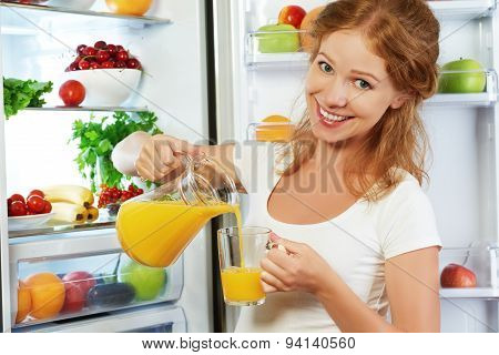 Happy Woman Drinking Orange Juice About Refrigerator