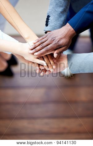 Close Up Of Colleagues' Hands Clasped Together