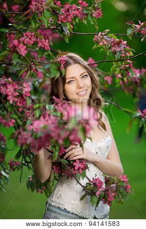 Young spring fashion woman in spring garden Springtime Summertime Trendy girl in the flowering trees in then at sunset in spring summer landscape background Allergic to pollen of flowers Allergy